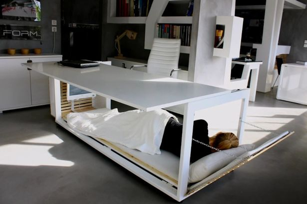 "Ever feel like you spend so much time in your office that you might a swell sleep there? Well, now there's a space-saving desk which ingeniously allows you to do just that. But you might not want to tell the boss about it in case you start getting more overtime. A Greek architect has designed the desk which converts to a bed, just the thing for those late-night office sessions. They told Archilovers : ""The main concept was to comment on the fact that many times our lives are 'shrinking' in order to fit into the confined space of our office. ""Eventually, I realized that each civilization may have a very different perception of things depending on its social context."""