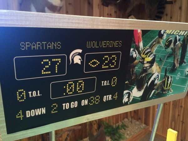 This photo taken Monday, Oct. 26, 2015, shows the scoreboard with an image of stuffed chipmunks portraying players on the final play of the Michigan State-Michigan NCAA college football game at the home of taxidermist Nick Saade in Lansing, Mich.  Michigan State's Jalen Watts-Jackson returned a fumble for the game-winning touchdown on Oct. 17. Saade tells the Lansing State Journal that the chipmunks were trapped by friends as nuisance animals. (Judy Putnam/Lansing State Journal via AP)  NO SALES; MANDATORY CREDIT