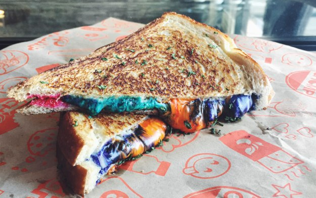 "Foodbeast- It seems the newest trend in food as arrived and it's multicolored. With the debut of the Rainbow Grilled Cheese a few weeks back, folks were bummed it was only available in Hong Kong. Not so much the case any longer as Chomp Eatery has unveiled their own version of the colorful dish. The LA-based restaurant is calling this one a Unicorn Melt. Chomp's new melt is made with White American and Provolone cheese, which they call ""Unicorn Milk."" The cheese goes through a fantastical transformation and the final result is served on toasted sourdough bread. You can get the Unicorn Melt at Chomp Eatery in Santa Monica for $6"